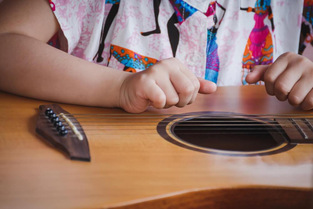 Kind zupft an Gitarre Musikschule